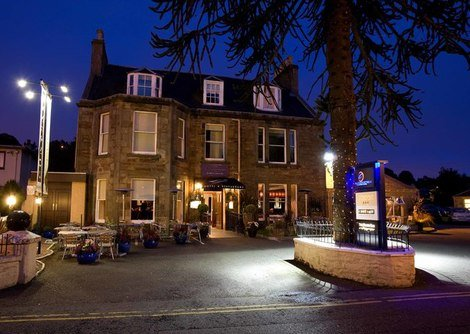 An exterior view set at night of the Glenmoriston Hotel in Inverness