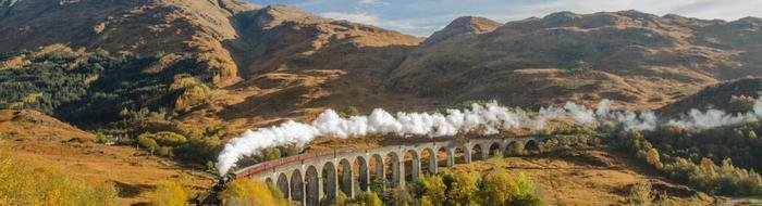 Summer view of the Jacobite steam train crossing the viaduct from Fort William to Mallaig.